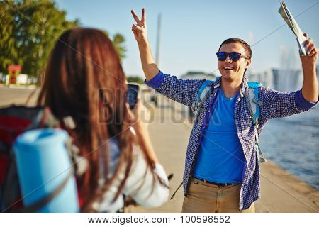 Modern woman with cellphone taking photo of her boyfriend outdoors