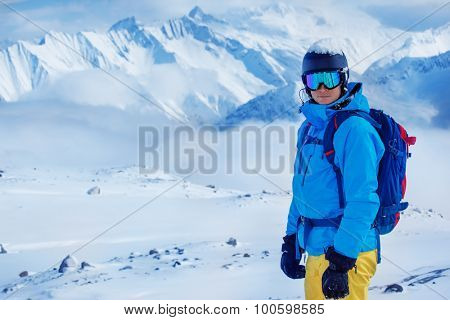 Portrait  of a young adult in a ski helmet and goggles, with high snowy mountains in the background