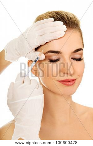 Young smiled woman is having facial botox injection,isolated on white.