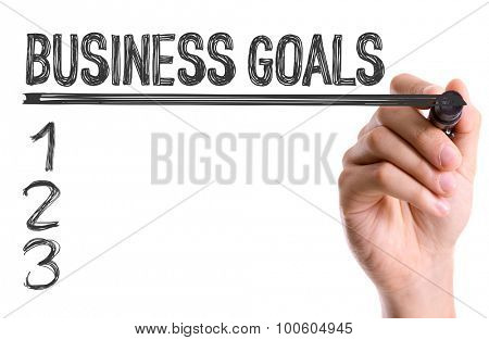 Hand with marker writing the word Business Goals