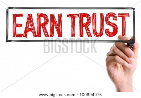 Hand with marker writing the word Earn Trust