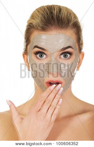 Young surprised woman with facial mask, isolated on white.