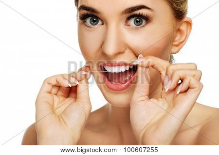 Young caucasian woman flossing her teeth, isolated on white