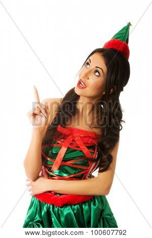 Surprised woman in elf hat pointing up.