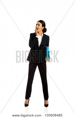 Surprised businesswoman holding a binder.