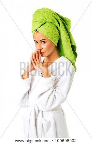 Pensive woman in bathrobe and towel on head.