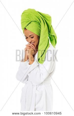 Spa woman in bathrobe clenching hands.
