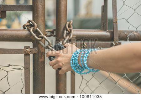 Hand Of Young Woman Grabbing Padlock