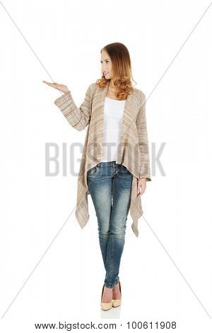 Beautiful casual woman showing empty hand.