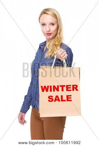 Woman with shopping bag and showing winter sale