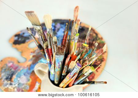 Artist paintbrushes and palette over light background