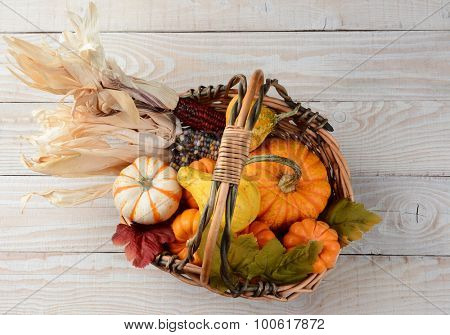 High angle view of an basket full of pumpkins, gourds, indian corn and leaves. The Autumn display is set on a rustic whitewashed wood table.