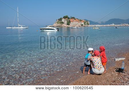 SVETI STEFAN, MONTENEGRO - JULY 08: mom and her children taking photos on the seashore of Sveti Stefan beach. The shot frames the beautiful landscape of sea and island of Sveti Stefan. Shot in 2015