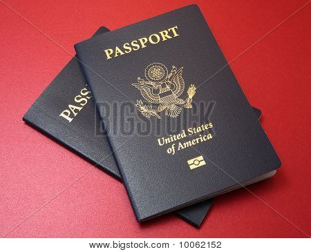 Two Us Passports On Red Background