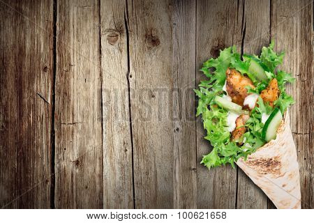 Tortilla chicken wrap sandwich on wooden background.