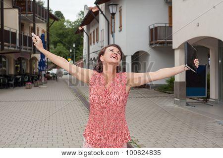 Joyful Woman With Open Arms On City Street