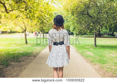 Woman Wearing Hat And Dress Walking In Park