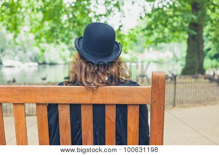 Woman Wearing Bowler Hat In Park On Bench