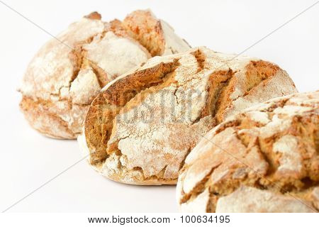 detail of three freshly baked loaves of bread on white background