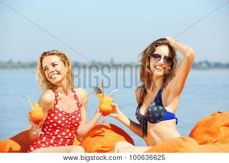 Two young girls enjoying cocktail on bag seats on beach at summertime