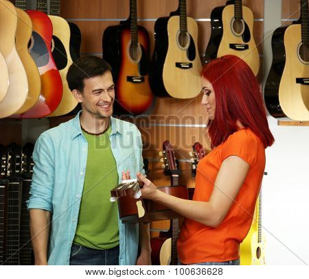 Beautiful young couple in music store