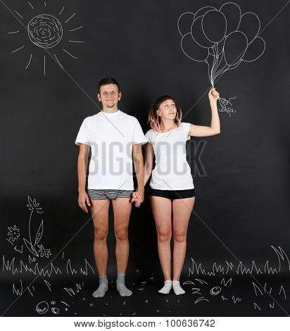 Young couple with balloons on black background