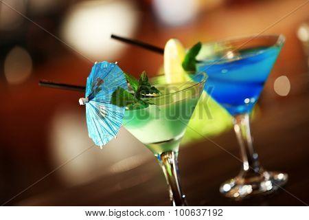 Glasses of cocktails on bar background