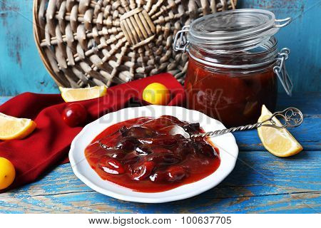 Tasty homemade plum jam in white plate on wooden table, closeup