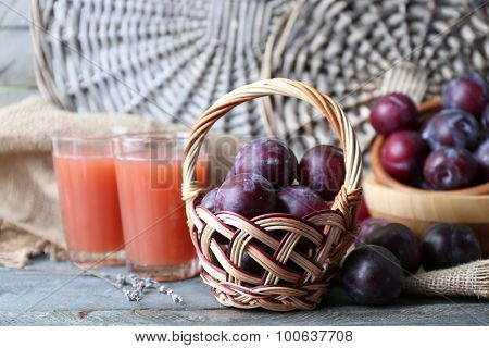 Delicious plum juice with fruits on wicker background