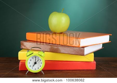 Stack of books with green apple and alarm clock on desk on green chalkboard background