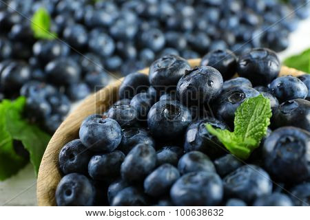 Tasty ripe blueberries with mint in bowl on table close up