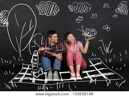Funny young couple in park on picnic, on black background