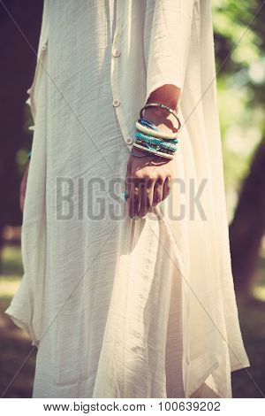 woman in long linen ivory color dress focus on hand with lot of bracelets outdoor shot natural light