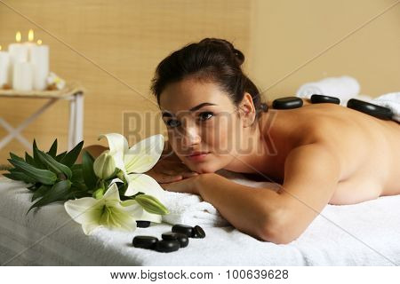 Young woman with spa stones on her back on massage table in beauty spa salon