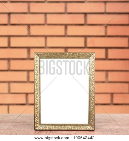 Old empty frame standing on table on brick wall background
