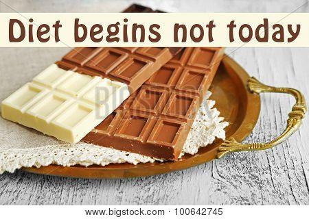 Chocolate bars on napkin, on tray and space for your text on wooden background