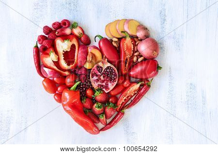 Collection of fresh red vegetables and fruits arranged in a heart shape on white rustic background strawberry raspberry pomegranate peppers capsicum chilli potato beans legumes