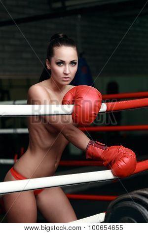 Half-naked brunette posing in red boxing gloves