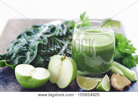 Juiced health juice in glass surrounded by cut up lime, ginger, apple, celery and spinach