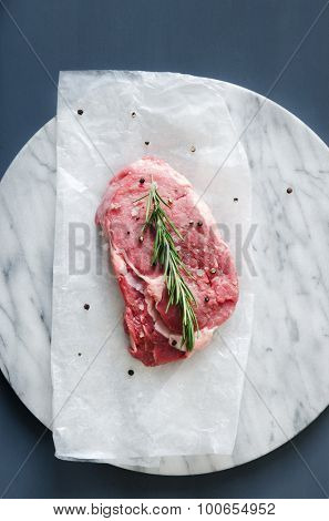 Raw beef steak on a grey marble surface against a dark background, overhead perspective