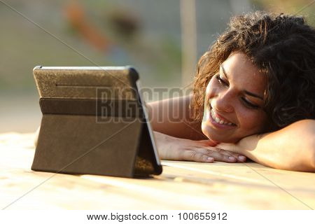 Woman Watching Videos On A Tablet At Sunset