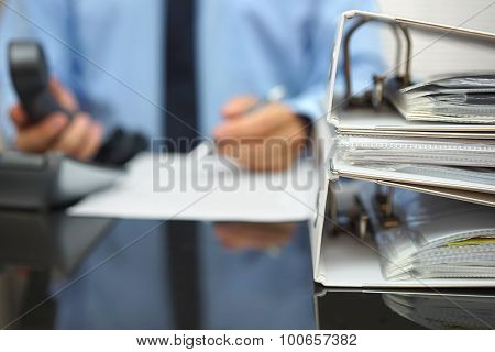 Businessman In Blur Is Working At Office Desk With Phone In His Hands And Document In Front If Him,