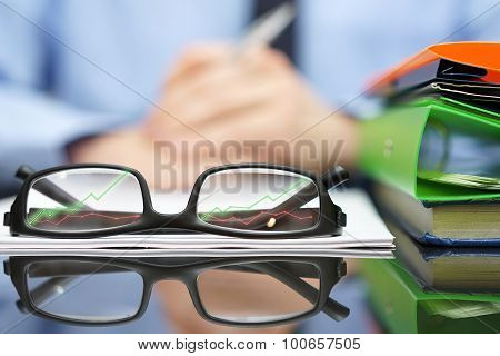 Financial Consultant In Background With Eyeglasses  In Front With Growing Arrows, Business And Succe