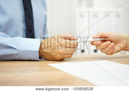 Businessman Give Pen To Business Client  To Sign The Contract With Binders In Background