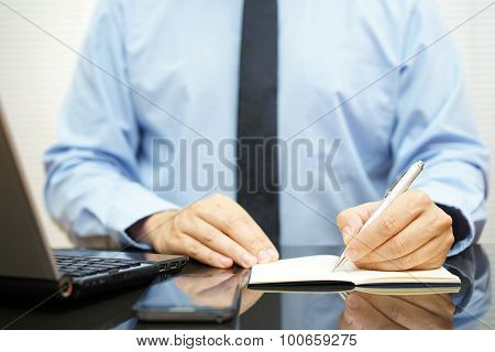 Businessman Take Notes On The Desk Next To Laptop Computer And Mobile Phone