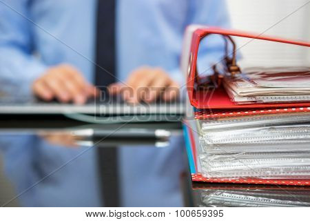 Accountant With Stack Of Invoices Is Inserting Data Into Computer Database