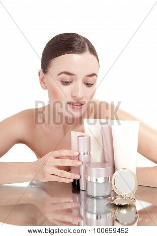 Young Woman With  A Well-groomed Skin Near The Creams Cosmetics. Skin Care Concept.