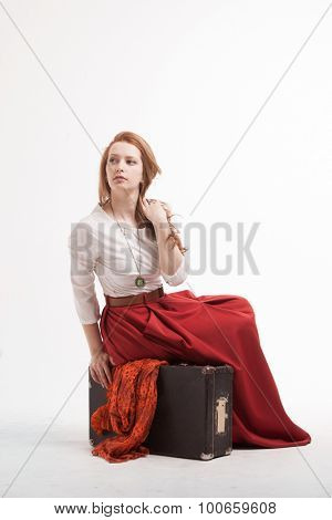Young Woman sitting on a suitcase, isolated on white background