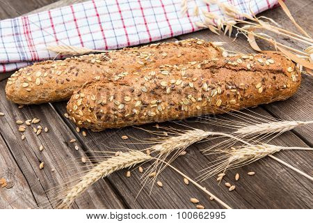 Rustic Baguette And Wheat On An Old Vintage Planked Wood Table.