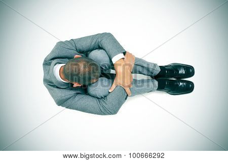 a businessman curled up in the floor with his head between his knees, slight vignette added